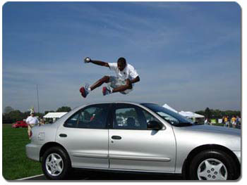 Chris Bryant, the Akron Car Jumper, easily leaps over one car and will soon try for a Guinness World Record by attempting to jump over five.
