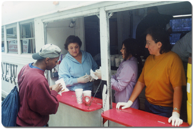 Jean joins other Relief Bus volunteers as they provide a meal and services to the needy.