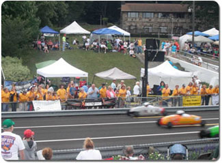 Johanna Barnowski's car, in the middle, wins a heat, cheered on by a sea of yellow shirts worn by IBOs and family.