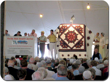 Ervin, center, is a skilled auctioneer, taking bids for an Amish quilt at the Florida event that also sold 50 homes for raising in Haiti.